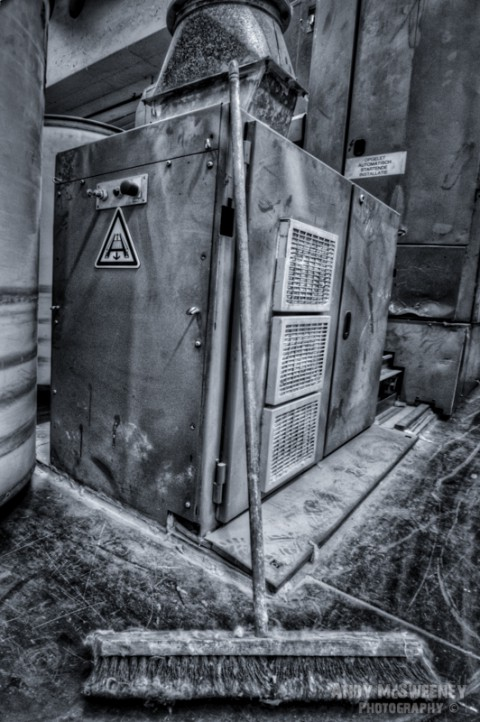 Black and white photo of a cotton processing machine and dusty broom in a closed cotton UCO factory in Brugge, Belgium.