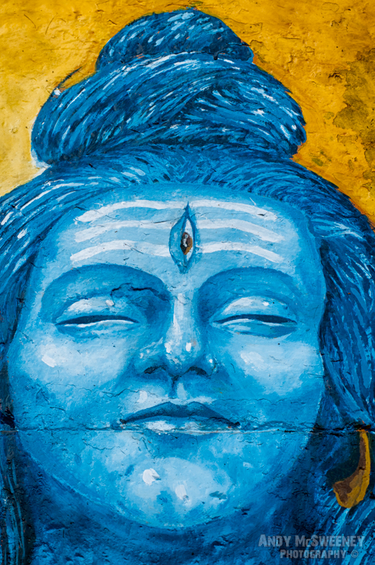 A colorful Buddha in blue and yellow with third eye adorns a wall in Varanasi, India