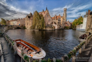 The Rozenhoedkaai with canal and bridge, boats, clouds, the Belfry and historical buildings in Brugge, Belgium.