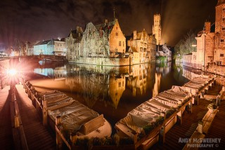 The Rozenhoedkaai at night with covered boats, streetlights, the Belfry, canals and reflections in Brugge, Belgium