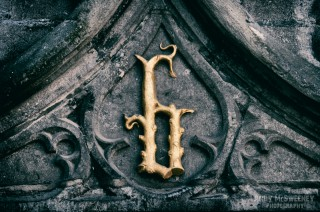 Gold 'B' for Brugge letter amongst the details of the Basilica of the Holy Blood on the Burg square in Brugge, Belgium