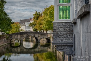 House with green stained Venetian glass and surrounding canals and bridge in Brugge, Belgium