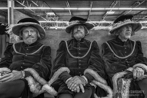 A black and white photo of three figurants in full costume waiting their turn at the rehearsal of the Holy Blood Procession in Brugge, Belgium 2015