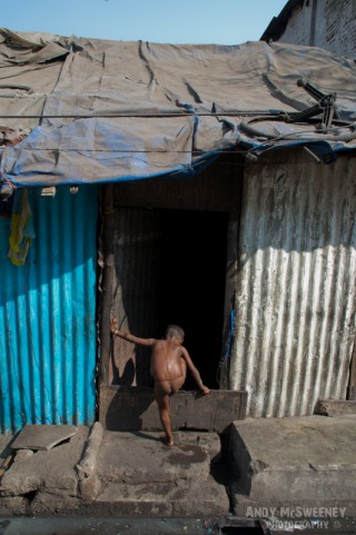Portrait of a little Indian boy with loin cloth crawling into the slums of his house in South-India, Mumbai