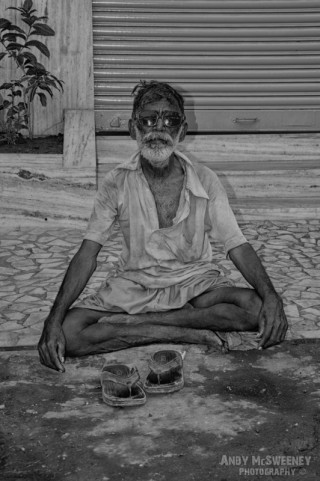 Black and white portrait of an Indian untouchable man with sunglasses in yoga pose on the streets of South-India, Mumbai