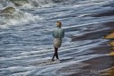 Colorful portrait of an Indian man in lungi and head cloth walking through the ocean water in South-India