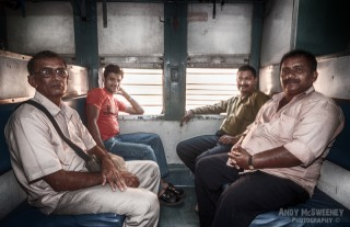 Portrait of four Indian men posing for the camera on a train in South-India