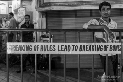 "Black and white street banner saying ""Breaking of Rules Leads to Breaking of Bones"" with surrounding people in India"