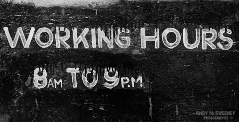 "Black and white street sign in India saying ""Working Hours 8am to 9pm"""