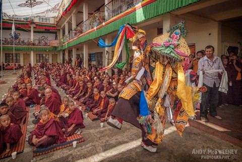 Colorful portrait of a dancer and surrounding little monks at a puja ceremony in the monastery of Bylakuppe, South-India