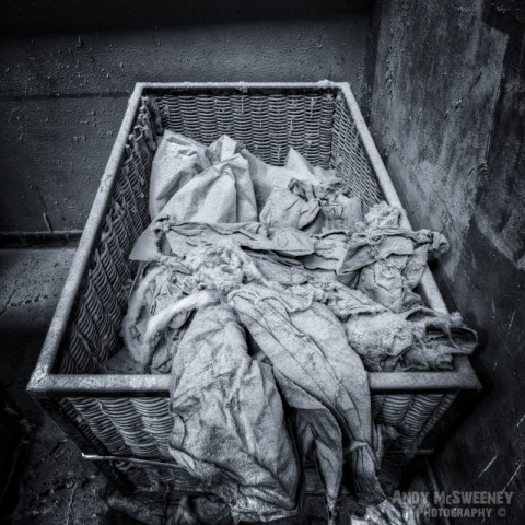 Black and white photo of a reet basket filled with old cotton in a closed cotton UCO factory in Brugge, Belgium.