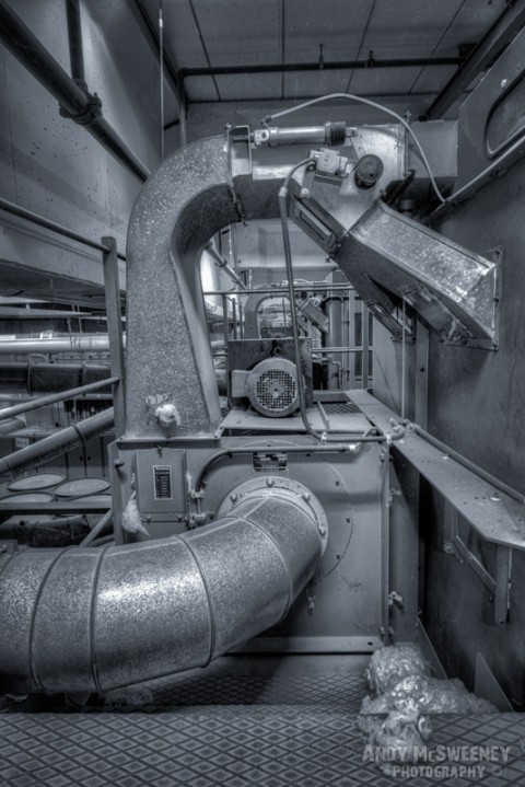 Black and white photo of a cotton processing machine in a closed cotton UCO factory in Brugge, Belgium.