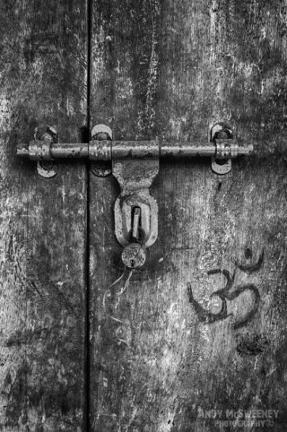 Close-up detail in black and white photo of an old wooden door with ohm symbol and iron handle in South-India