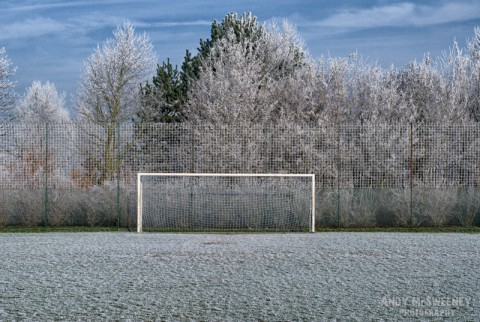 Landscape of blue skies and clouds, a football field and trees covered in frost during winter in Brugge, Belgium