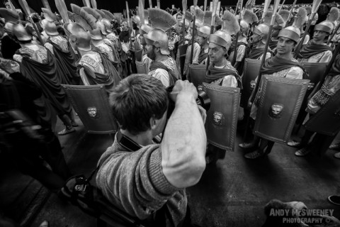 A black and white photo of a photographer shooting an army of knights passing by at the Holy Blood Procession in Brugge, Belgium 2015
