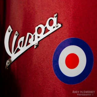 A close-up of the Vespa sign and a sticker on a Vespa scooter during Mod Days Brugge, Belgium