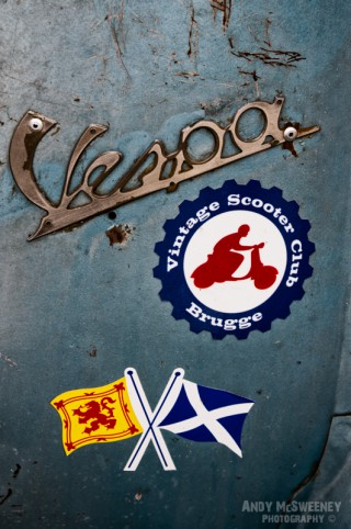 A close-up of the Vespa sign and stickers on a vintage Vespa scooter during Mod Days Brugge, Belgium