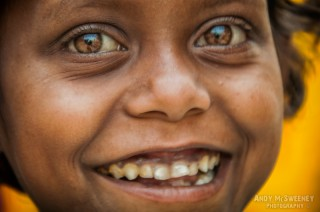 Close-up portrait of a beggar child giving the big eyes and big smile for the camera in South-India
