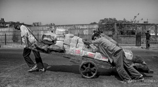 Selective color portrait of three boys pushing a heavy cart loaded with Tuff Brand packages up the hill in Mumbai, South-India