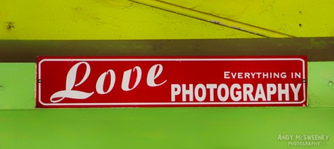 "Colorful street advertising sign saying ""Love Everything in Photography"" in Margao, India"