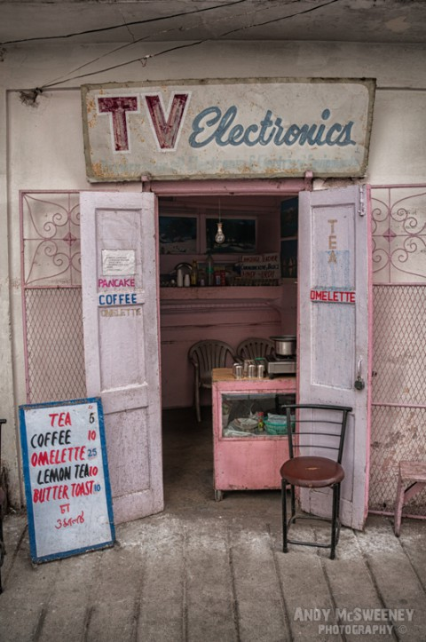 "Colorful shop with old advertising sign offering ""TV Electronics"" and drinks and snacks in India"