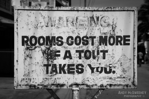 "Old black and white street sign in Mamalapuram India warning ""Rooms Cost More if A Tout Takes You"""