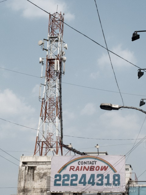 "Street sign in India saying ""Contact Rainbow"" with street lamps and tower."