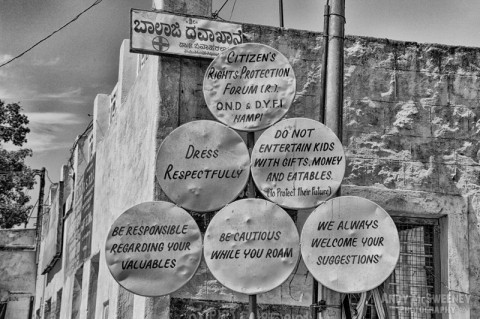 "Six black and white street signs in Hampi, India regarding ""Citizen's Rights Protection"""