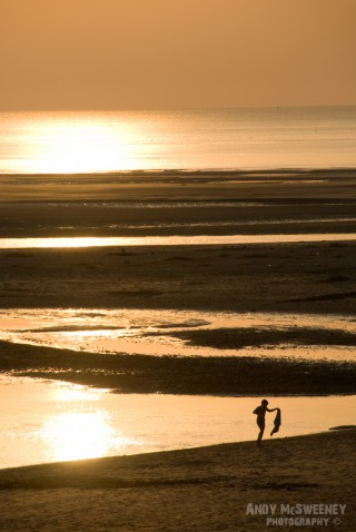Boy walking the beach at sunset in Zeeland, The Netherlands
