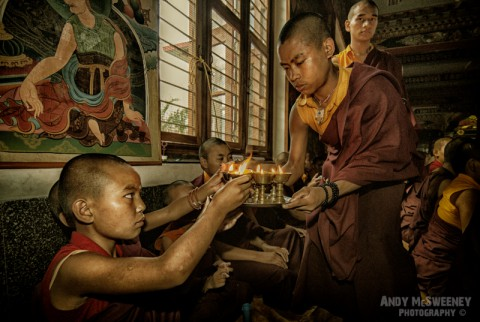 Colorful portrait of praying monks with candle during a puja ceremony in the monastery of Bylakuppe, South-India