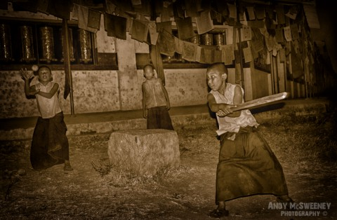Sepia portrait of little monks playing cricket under the prayer flags in the monastery of Bylakuppe, South-India