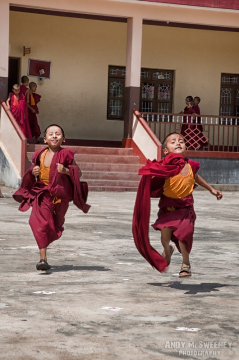 Colorful portrait of two little monks running during recess in the monastery of Sera, South-India