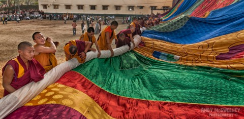 Colorful portrait of monks rolling out the giant thangka for a puja ceremony in the monastery of Bylakuppe, South-India